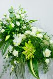 A bouquet of white roses, yellow daffodils, greenery and lotuses stands in a vase on a marble stand Stock Photography