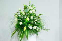 A bouquet of white roses, yellow daffodils, greenery and lotuses stands in a vase on a marble stand Stock Images