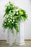 A bouquet of white roses, yellow daffodils, greenery and lotuses stands in a vase on a marble stand Royalty Free Stock Photos