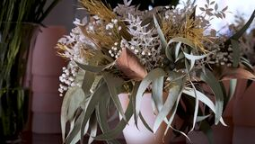 Bouquet with white statice flower, eucalyptus, green, brown, golden plants and leaves.