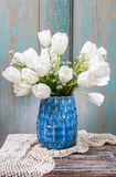 Bouquet of white tulips in blue ceramic vase Royalty Free Stock Photo