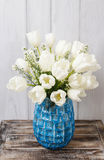 Bouquet of white tulips in blue ceramic vase Stock Images