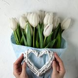 A bouquet of white tulips in blue wrapping paper with woman hands and heart on a white concrete background. Top view. Flat lay. Postcard for Easter, Mother`s Royalty Free Stock Images