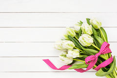 Bouquet of white tulips decorated with ribbon on white wooden background. Top view Stock Photos