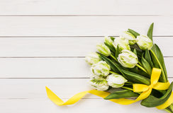 Bouquet of white tulips decorated with yellow ribbon on white wooden background Stock Image
