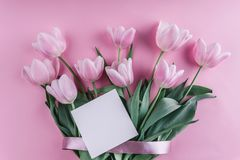 Bouquet of white tulips flowers and sheet of paper over light pink background. Greeting card or wedding invitation. Flat lay, top view, copy space stock photo