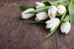 Bouquet of white tulips on a blue wooden table. Bouquet of white tulips on a grey wooden table, copy space. Easter Royalty Free Stock Image