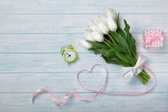 A bouquet of white tulips and a pink ribbon in the form of a heart with a gift and an alarm clock on the hobs royalty free stock images