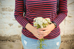 A bouquet of white wildflowers in the hands of a girl Stock Photo