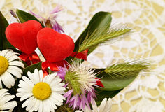 Bouquet of wid flowers and two hearts on crochet background Stock Image