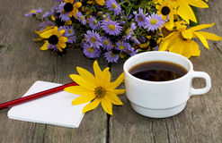 Bouquet of wild flowers, coffee and pencil with paper Stock Image