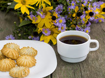 Bouquet of wild flowers, coffee and plate with baking Royalty Free Stock Image