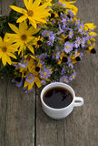 Bouquet of wild flowers and cup of coffee on a wooden table, the Stock Image