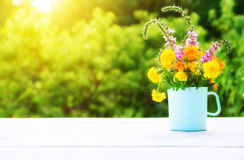 Bouquet of wild flowers in  cup on wooden table on a background Royalty Free Stock Images