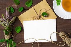 Bouquet of wild flowers, envelope and cup of tea on wooden background Royalty Free Stock Photography
