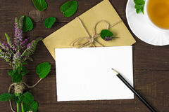 Bouquet of wild flowers, envelope with pencil and cup of tea on wooden background Royalty Free Stock Photography