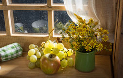 Bouquet of wild flowers with grapes and an apple Stock Image