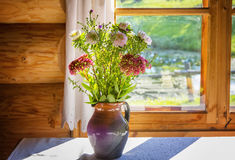 Bouquet of wild flowers in a jug at the window. stock photos