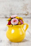Bouquet of wild flowers in yellow jug, copy space Stock Image
