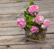 Bouquet of wild rose in vintage style on basket Stock Images
