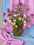 Bouquet of wildflowers. Bouquet of wild flowers in a vase on draperies stock photos