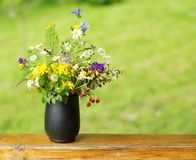 Bouquet of wildflowers and strawberry berries stand on the terrace Royalty Free Stock Photos