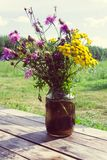 A bouquet of wildflowers on a wooden table in a summer village stock photography