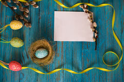Bouquet willow branch and Easter eggs on a wooden table Royalty Free Stock Photos