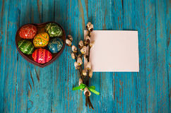 Bouquet willow branch and Easter eggs on a wooden table Stock Photos