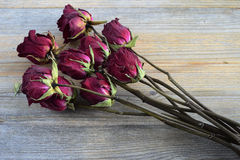 Bouquet of withered roses on a wooden Stock Photos
