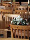 Bouquet and wooden chairs. Focus on a bouquet of flowers amongst rows of timber chairs and tables. Ready for a party or event Royalty Free Stock Photos