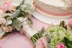 Bouquet wrapped in roserie next to wedding cake.. Wedding roses in a bouquet wrapped in ribbon and a roserie in front of a cake Royalty Free Stock Photos