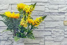Bouquet of yellow artificial flowers on a stone wall background.  stock photos