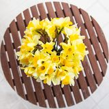 Bouquet of yellow daffodils in a white vase on a wooden table outdoor. Close-up, flat lay royalty free stock photo