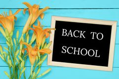 bouquet of yellow flowers and a frame with an inscription back to school on a turquoise wooden background royalty free stock image