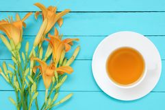 Bouquet of yellow flowers hemerocallis and white cup on saucer with green tea on a turquoise wooden background. View from abov royalty free stock images