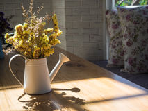 Bouquet of yellow flowers in watering can on wooden table Stock Image