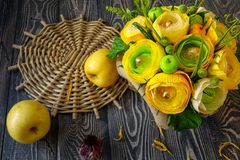 Bouquet of yellow-green paper flowers with candies inside and apples on a gray wooden background stock photo