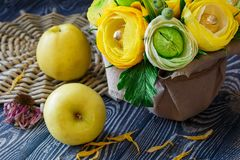 Bouquet of yellow-green paper flowers and sweets on a gray wooden background royalty free stock photography