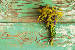 A bouquet of yellow and green wildflowers on the blue and white wooden background, top view. Stock Image