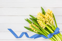 Bouquet of yellow hyacinths decorated with blue ribbon on  white wooden background. Top view Stock Photos