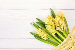 Bouquet of yellow hyacinths decorated with lace on  white wooden background Stock Image