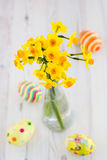 Bouquet of yellow lent lilly (daffodil) with easter eggs on a wo Royalty Free Stock Photos
