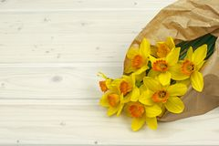 Bouquet Yellow narcissus flowers in paper on table stock image