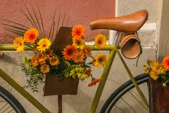 Bouquet of yellow and orange flowers on the bicycle Stock Photos