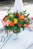 Bouquet of Yellow and Orange Flowers in glass Vase on white Decorative Table at Birthday Party background royalty free stock photo