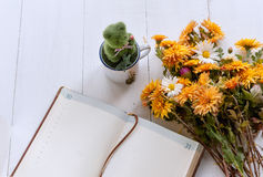 Bouquet of yellow and orange flowers on a white wooden table. Next to a notebook with leather cover Stock Photos