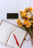 Bouquet of yellow and orange flowers on a white wooden table. Next to a notebook with leather cover Royalty Free Stock Photography