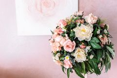 Bouquet of yellow and pink flowers against the background of the image of a rose on a pink wall. Bouquet of yellow and pink flowers against the background of a royalty free stock image