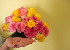 Bouquet of yellow and pink roses and ring on the woman's hand on a light-yellow background. royalty free stock photography